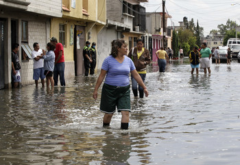 A resident walks on a flooded street in Nezahualcoyotl near Mexico City
