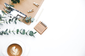 Flay lay, Top view office table desk. Feminine desk workspace frame with clipboard, green leaves eucalyptus  and coffee  on white background.  ideas, notes or plan writing concept