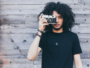 African american man with typical afro hair takes a picture of a vintage camera against a background of old boards
