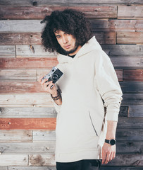 African american man with afro hair posing with vintage camera on colourful background of old boards. Dressed in a cool white outfit. Afrohair.