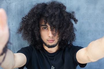 Handsome young African man making selfie while standing against grey background. Afro hair.