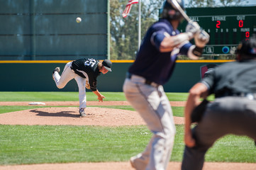 Mens' baseball pitcher throwing the curveball to the batter.