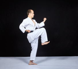 Block by hand and blow leg is training the athlete in karategi