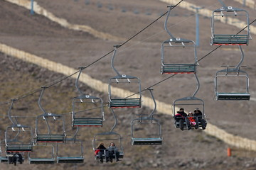 Tourists ride the chairlift at the El Colorado ski centre at Los Andes Mountain range, near Santiago