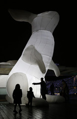 "People look at art installation ""Intrude"", featuring giant illuminated white rabbits, in central London"
