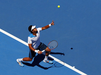 Jo-Wilfried Tsonga of France serves to Thomaz Bellucci of Brazil during their men's singles match at the Australian Open 2014 tennis tournament in Melbourne