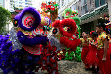 Filipino-Chinese students look at lion and dragon dancers after performing traditional dances ahead of the Lunar New Year celebrations at Lucky Chinatown Mall in Binondo city, metro Manila