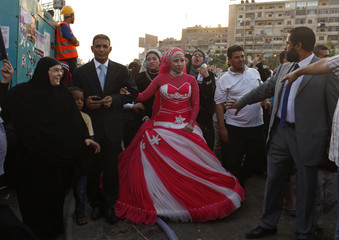 A newly wed couple, supporters of deposed Egyptian President Mursi, walk to the stage of the sit-in area around Raba' al-Adawya mosque