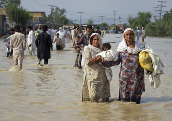 Women wade through flood waters with their children while evacuating from Nowshera Pakistan