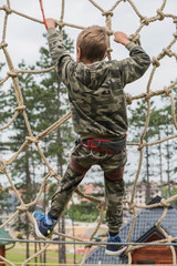 Small boy climbing rope spider's web in outdoor adventure park