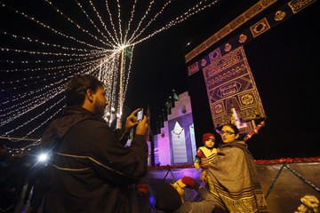 Man uses a mobile phone to take a photo of his family in front of a religious monument, during a celebration to mark Eid-e-Milad-ul-Nabi, the birth anniversary of Prophet Mohammad, in Karachi