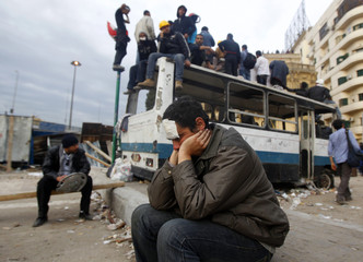 An injured anti-government protester rests by a burned out bus, used as barricade, alongside the Egyptian Museum near Tahrir Square in Cairo