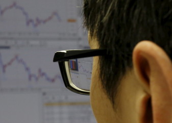 An employee of a foreign exchange trading company works in front of a monitor displaying the graphs of the recent fluctuations of the Japanese yen's exchange rate against various currencies in Tokyo