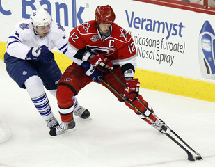 Toronto Maple Leafs' Luke Schenn battles Carolina Hurricanes' Eric Staal for the puck during their NHL hockey game in Raleigh
