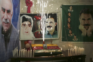 A birthday cake is seen near the picture of jailed Kurdish militant leader Abdullah Ocalan of the Kurdistan Workers Party to commemorate his birth anniversary in Aleppo's Sheikh Maqsoud neighbourhood