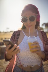 Young woman listening to music while having drink