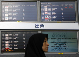 """A woman walks past screens showing flight information and a """"Pray for MH370"""" sign at Kuala Lumpur International Airport"""
