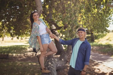 Portrait of smiling couple playing on tree trunk