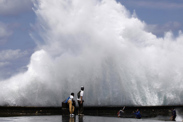 """Students play as waves crash on Havana's seafront boulevard """"El Malecon\"""