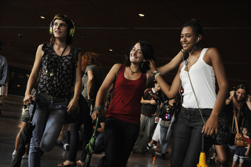 """Three women in """"Experimento mp3"""" simultaneously act out instructions given via their headphones in a group action organised by Improv Everywhere in Bilbao"""