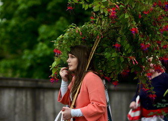 A woman carries a fuschia plant on the final day of the Royal Horticultural Society's Chelsea Flower Show in London