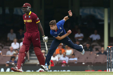 Chris Woakes of England bowls next to Lendl Simmons of the West Indies during their warm-up match at the Sydney Cricket Ground
