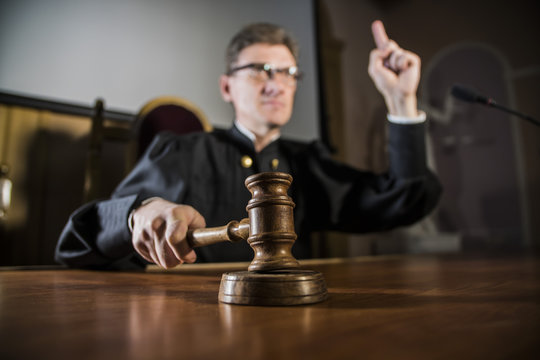 a judge with a hammer in his hand in the court room