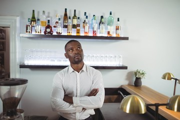 Thoughtful bar tender standing with arms crossed at bar counter