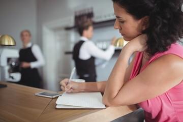 Woman writing on a diary at bar counter