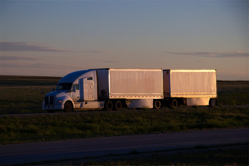 A white Kenworth sleeper truck pulls a set of white pup doubles down a rural US highway during sunset hours. All visible trademarks and markings have been removed.