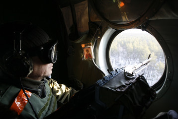 A member of the Ukrainian armed forces keeps his weapon at the ready as he looks out of a helicopter while flying above Kharkiv region