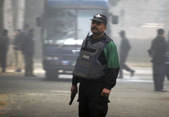 A Pakistani police commando holds his weapon as he stands guard near a police van carrying five Americans arrested in Pakistan in Sargodha