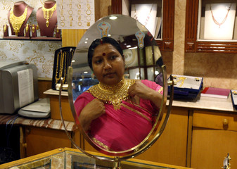 A woman is reflected in a mirror as she tries on a necklace at a jewellery showroom on Akshaya Tritiya, a major gold buying festival, in Kolkata