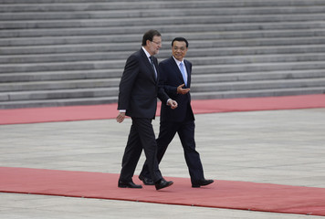 China's Premier Li chats with Spain's Prime Minister Rajoy as they attend a welcoming ceremony outside the Great Hall of the People, in Beijing
