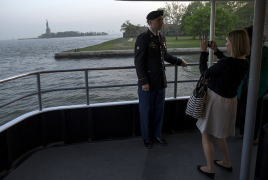 Vasily Sergeevich Sirotin, originally from Russia and an active U.S. Army Reserve specialist is photographed by his wife in front of the Statue of Liberty after becoming a United States Citizen in a naturalization ceremony at Ellis Island in New York Harbo