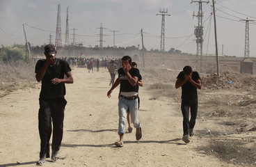 Palestinian protesters run away after Israeli troops fired tear gas canisters during clashes following a protest in solidarity with Al-Aqsa mosque near the border with Israel, east of the Gaza Strip