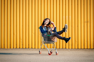 Cheerful stylish young girl in jeans jacket, shoes and skirt, listening to music in headphones with phone, in sunny day sitting in shopping cart for supermarket. With space for text