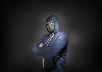 Hacker with arms crossed behind a mask