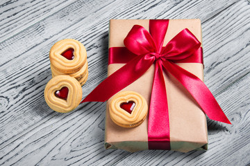 Gift box with satin bow and cookies with marmalade in the shape of heart. A romantic gift. Present on a gray background.