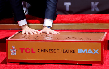 Director Michael Bay places his hands in cement during a ceremony in the forecourt of the TCL Chinese theatre in Los Angeles
