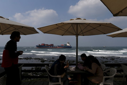 Tourists eat lunch at a cafe in front of a damaged Taiwanese TS Lines Co cargo ship, which was carrying 447 tonnes of fuel oil, off the coast of New Taipei City