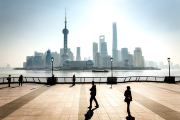 Les buildings de Shanghai en contre jour avec des promeneurs en ombre chinoise sur un parvis