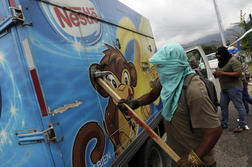 Masked protesters block a truck carrying ice cream during a protest in support of missing students of Ayotzinapa Teacher Training College Raul Isidro Burgos on a highway near of Chilpancingo