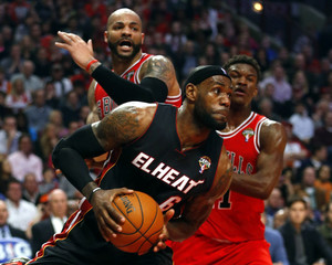Miami Heat's LeBron James takes the ball to the basket by Chicago Bulls' Carlos Boozer and Jimmy Butler during the first half of their NBA basketball game in Chicago