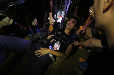 Local broadcast journalist reacts after being injured during clashes that broke out between protesters and riot police at Mongkok shopping district in Hong Kong