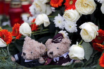 Two teddy bears dressed in the uniforms of Germanwings sit in the centre of a wreath outside the Germanwings headquarters at Cologne-Bonn airport