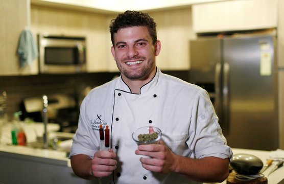 Chef Sayegh holds marijuana buds and THC (Tetrahydrocannabinol) and CBD (Cannabidiol) oils as he poses in his kitchen in Los Angeles