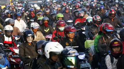 People ride motorcycles as they return to their hometown in Cibitung district, West Java
