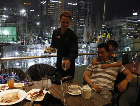 A waiter cleans the table for a customer as construction work is going on in the background in Manila