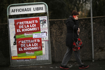 A woman walks in front of a banner against the labour reform bill proposal in Vertou